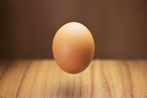 Close up of egg hovering over counter