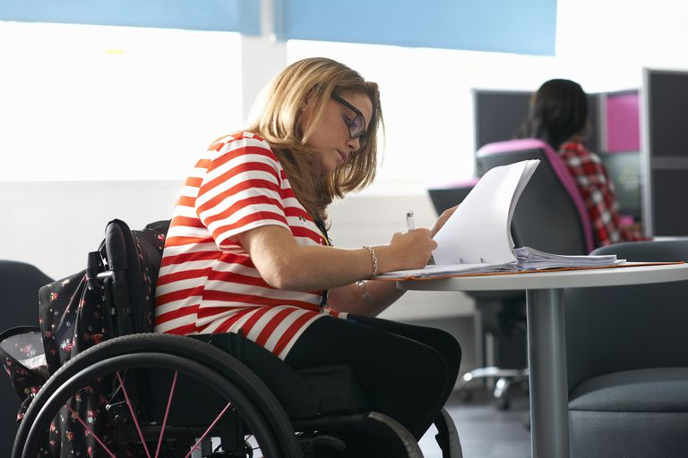 Teenage girl in wheelchair studying