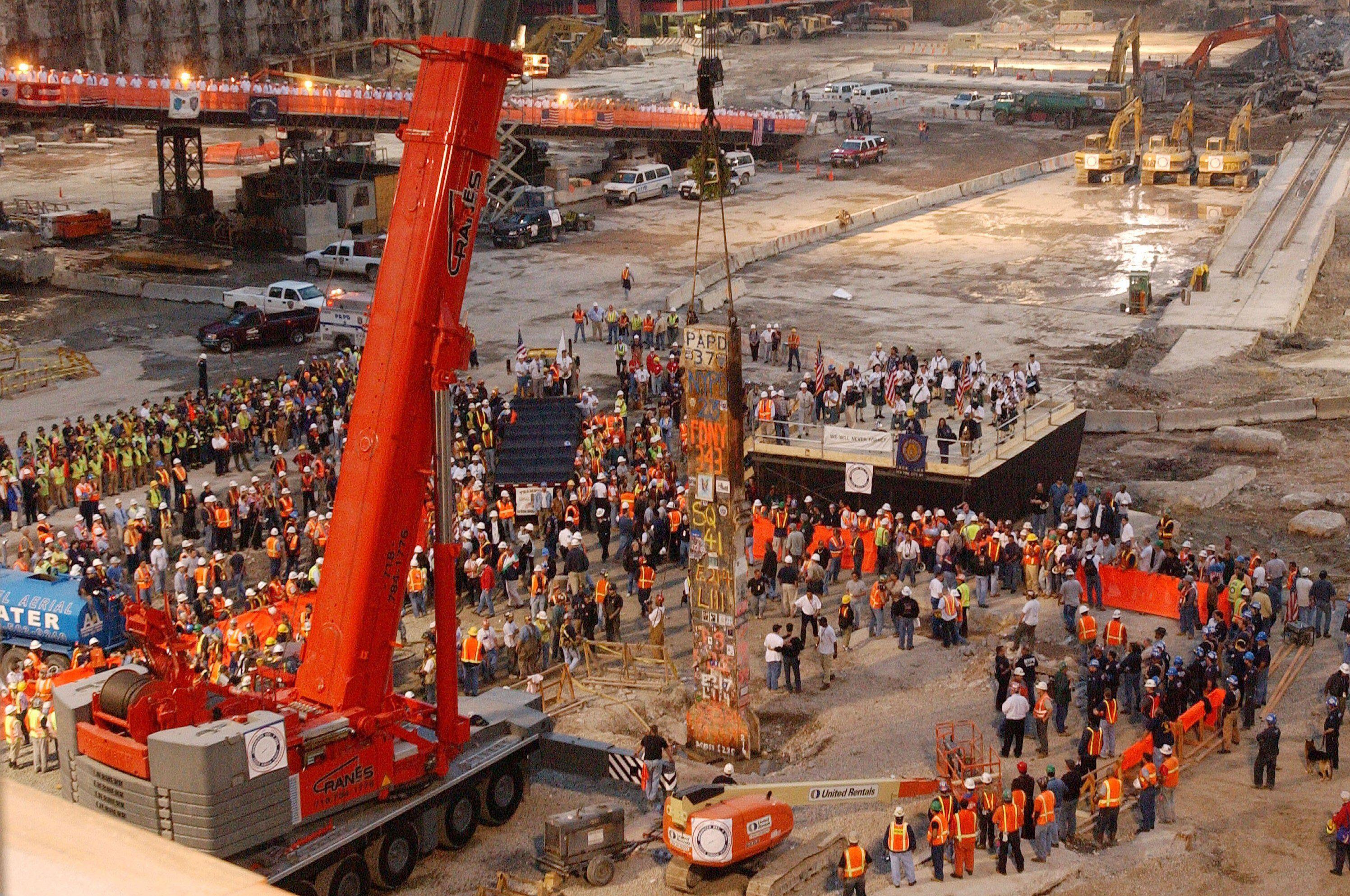 construction site crane with broken beam, workers surrounding it, platforms overlooking ceremony