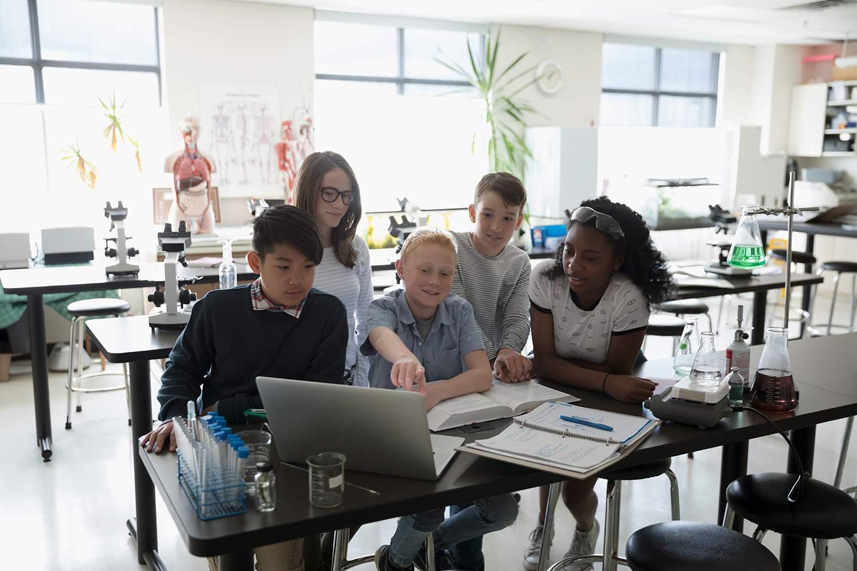 Mittelschüler, die wissenschaftliche Experimente am Laptop im Wissenschaftslabor durchführen