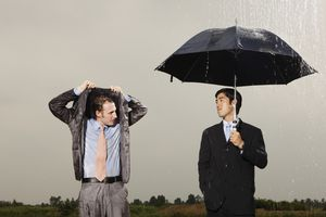 man with umbrella looking at man standing in the rain