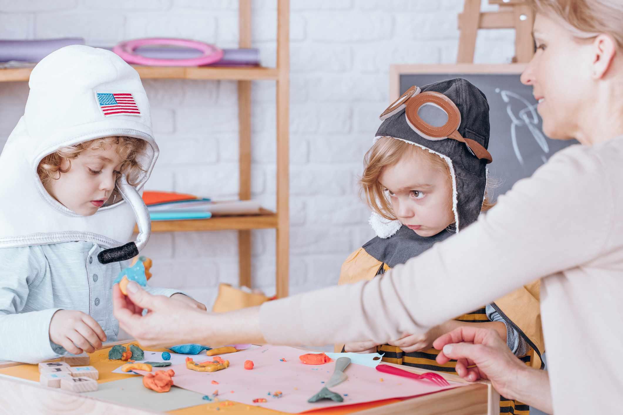 ハロウィンコスチュームを着ている生徒と遊ぶ幼稚園の先生