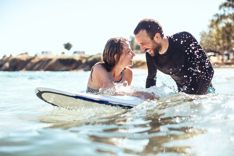 man and woman smiling on surfboard
