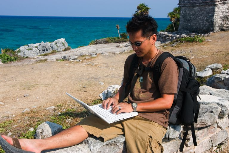 Man outdoors with computer.