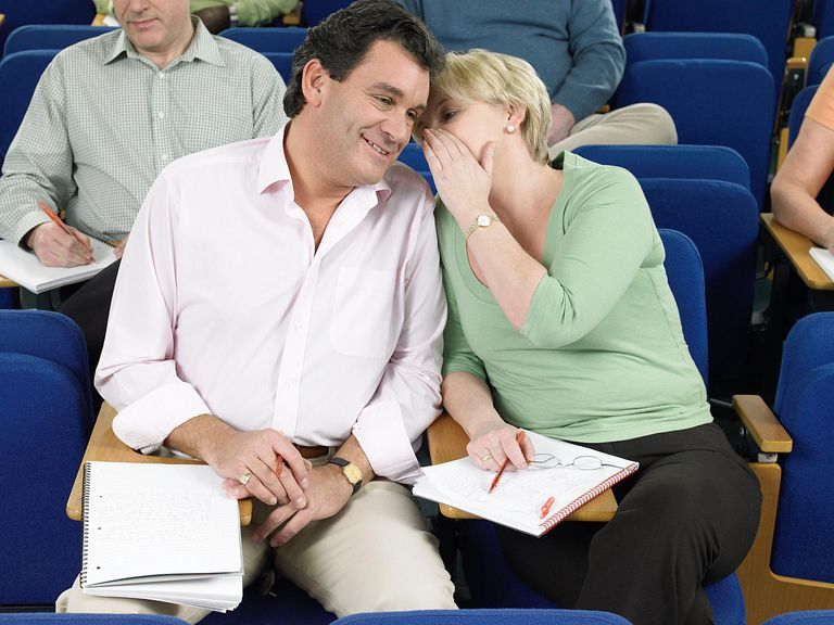 man and woman whispering in class