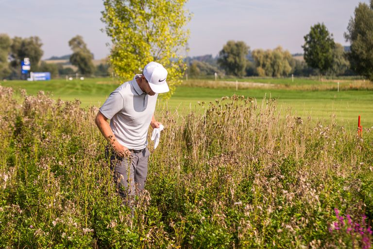Pro golfer Lucas Bjerregaard searches for his golf ball during a European Tour tournament.