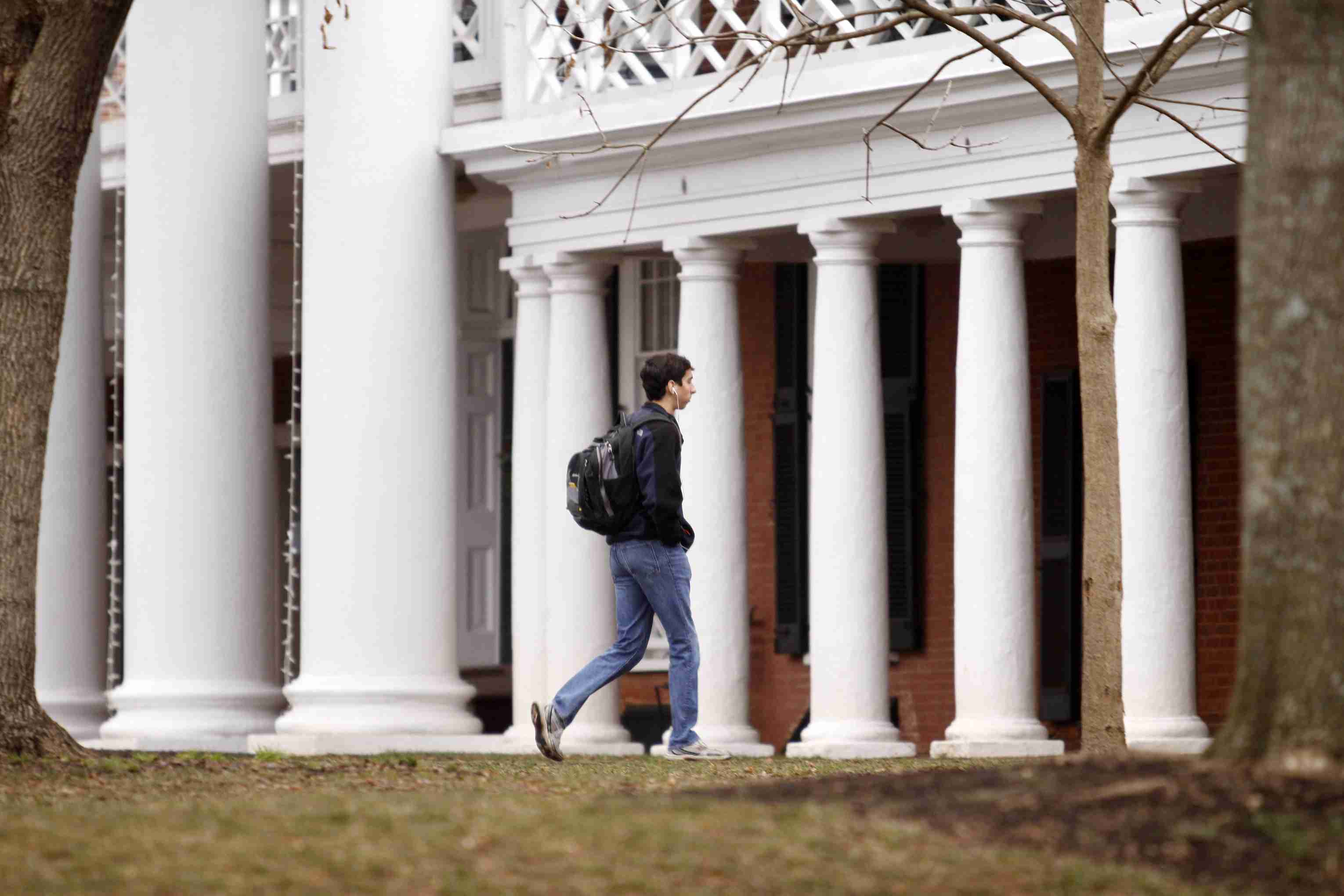 student walking on a college campus near Tuscan columns