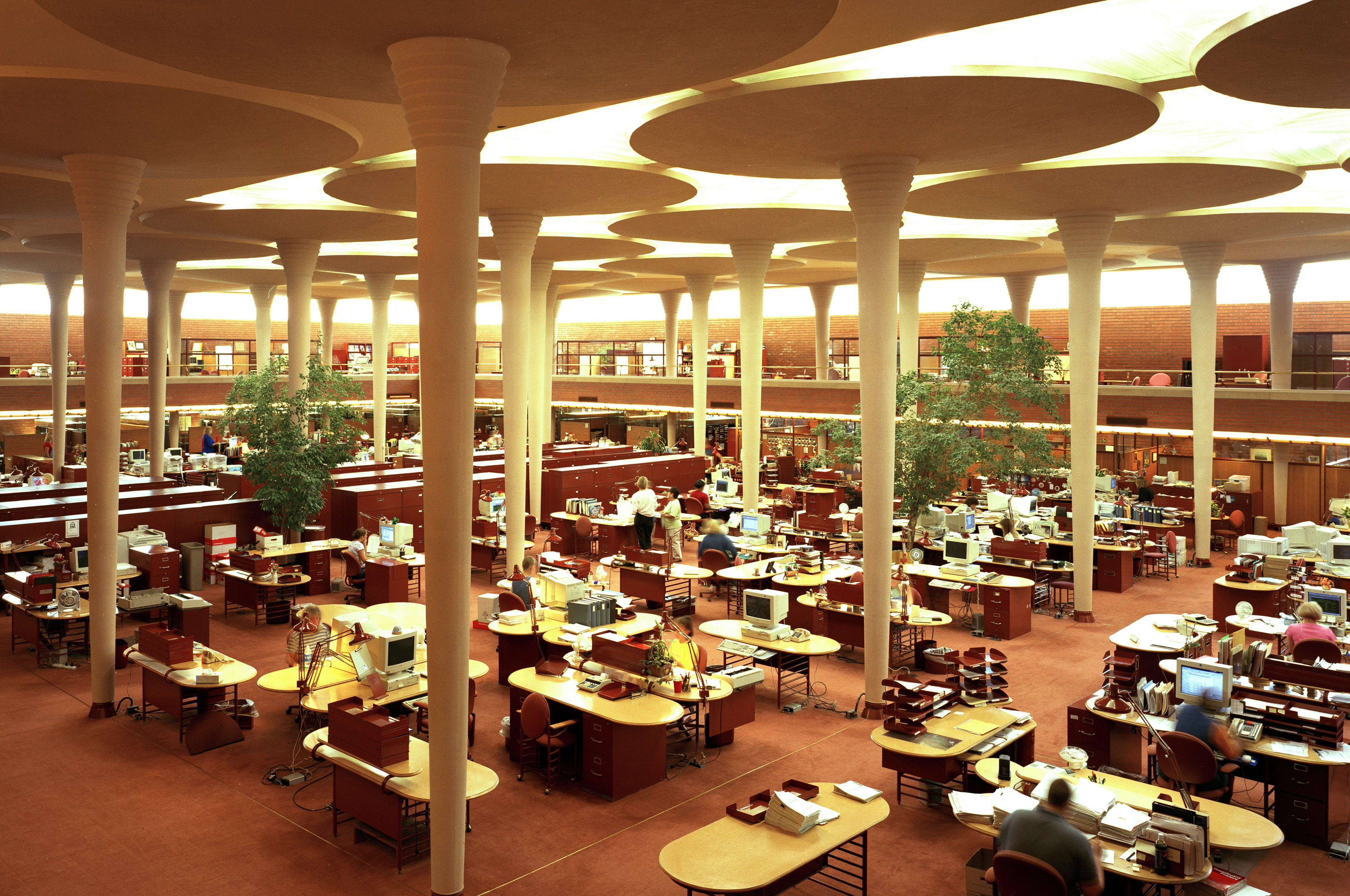 oval desks arranged in an open space, well-lit, with space-age looking columns topped with thin mushroom-like capitals