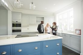 a saleswoman or estate agent shows a couple around a home with new kitchen