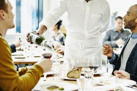 Waiter pouring wine for men at a restaurant.