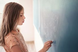 student solving math problems on chalkboard