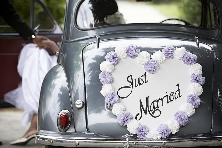 "A couple enters a vintage car with a ""just married"" sign after their wedding."