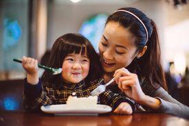 Mom & toddler girl having cake joyfully in cafe