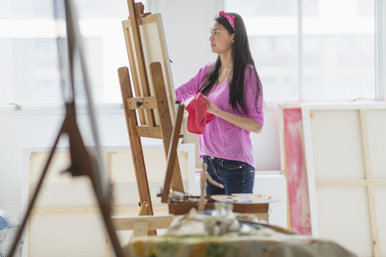 Mixed race teenage girl painting in studio