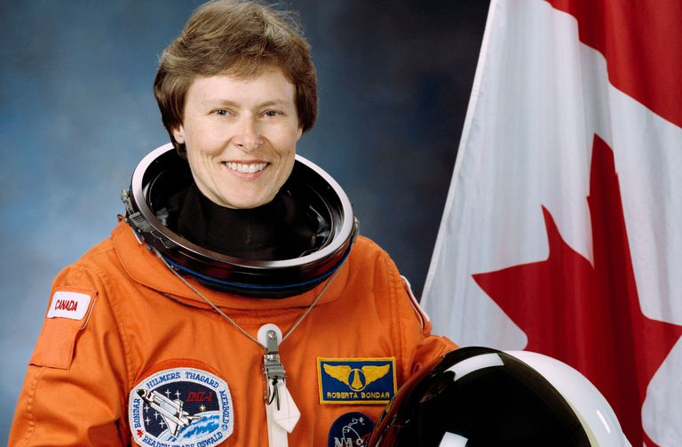 Color photograph of Roberta Bondar in space suit next to Canadian flag.