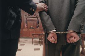 Businessman in handcuffs in courtroom