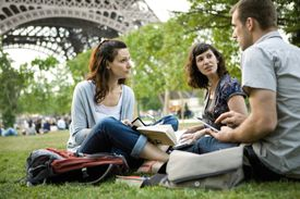 Group of people talking as they sit under the Eiffel Tower.