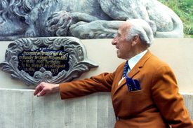 White-haired Sir Clough Williams-Ellis, 90, in orange-brown suit looking at a plaque with ornate cast-iron framing in 1973