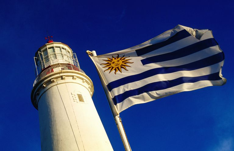 Uruguayan flag next to lighthouse.