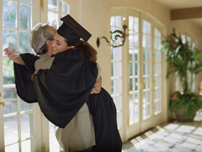 Young female graduate hugging an elderly man