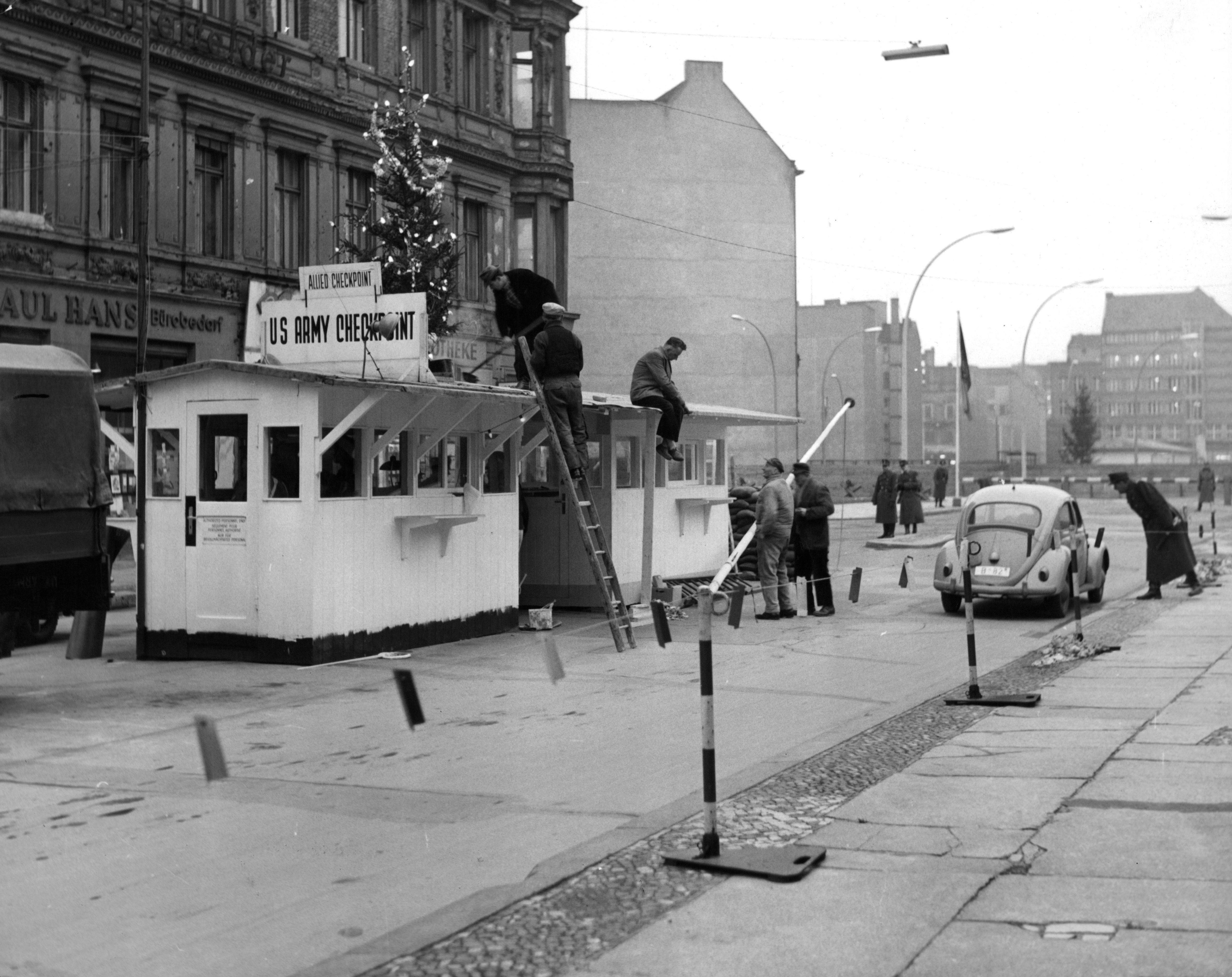 Men decorating a tree for Christmas at Checkpoint Charlie in Berlin