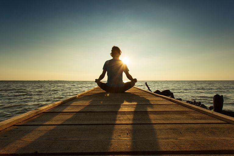 Woman meditating on a dock