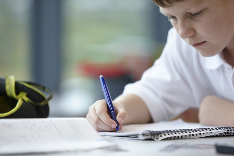 Close up of schoolboy writing in class