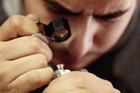 Jeweler inspecting gemstone with loupe