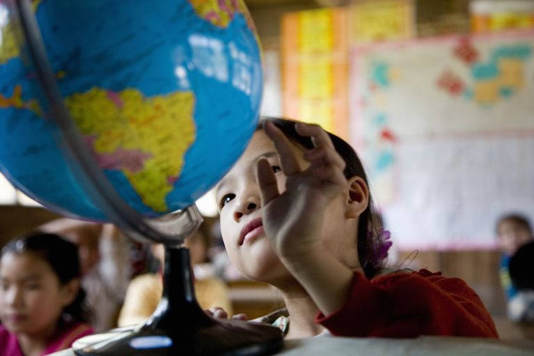 Girl looking at a globe in a classroom.