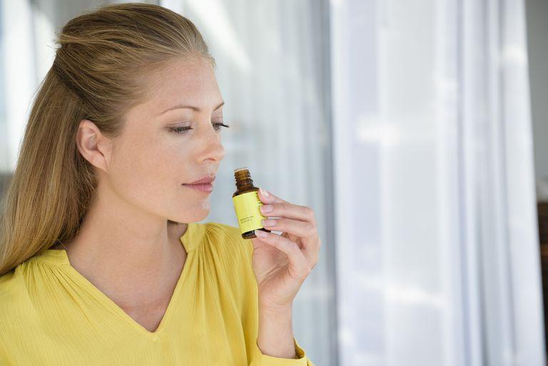 woman smelling a bottle of tea tree oil