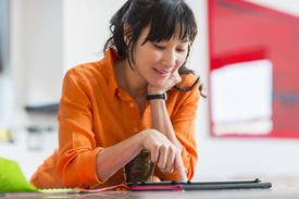 Asian woman using tablet computer in kitchen