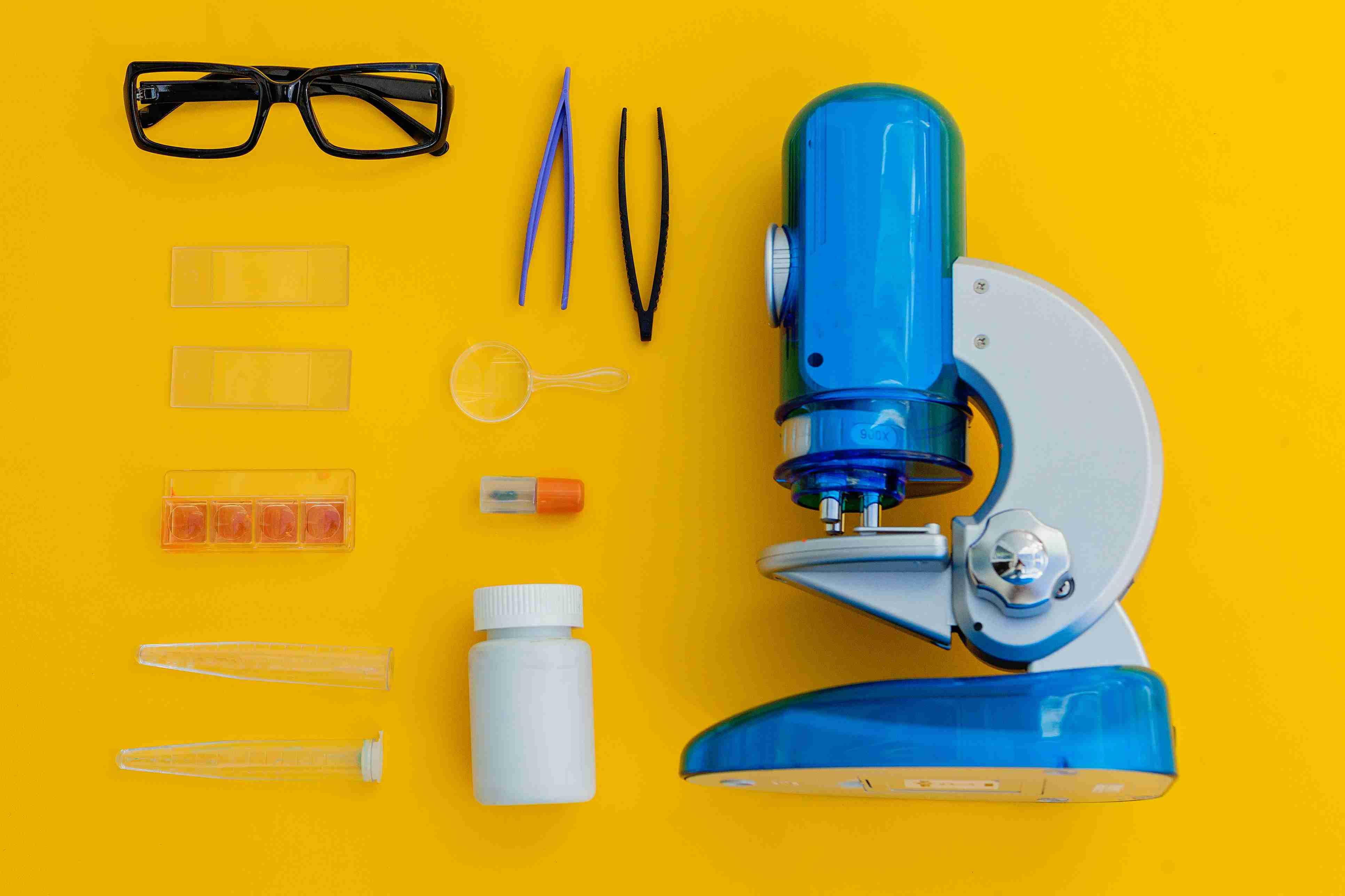 Microscope and related objects used every day by scientists, including tweezers and microscope slides