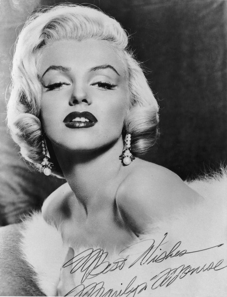 Picture of Marilyn Monroe wearing a fur stole around her bare shoulders.