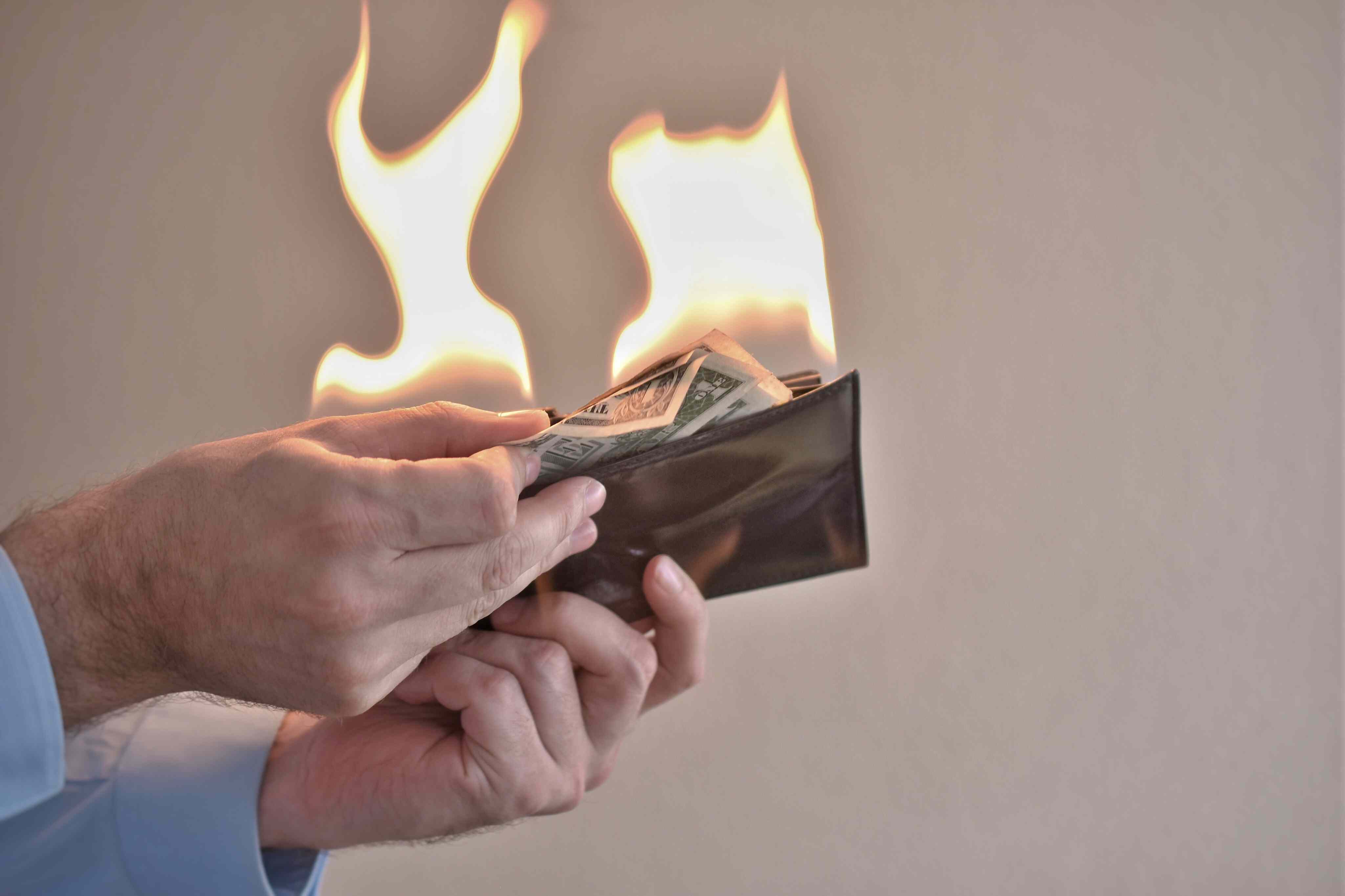 Cropped hands of man removing burning paper currencies from wallet