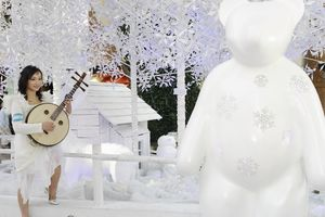 Woman playing traditional Ruan by large white teddy bear