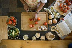 Overhead view woman cutting tomatoes on cutting board.