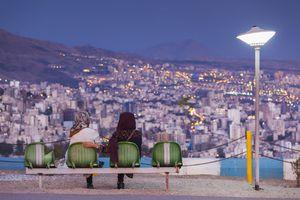 People sitting in Iran Park above the Iran, Tehran city skyline