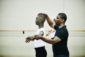 Ballet instructor adjusting dancers form