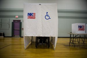 Person in a wheelchair voting in a handicap accessible voting booth