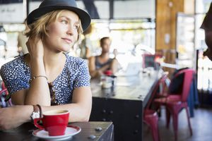 Pensive woman in hat with coffee looking away in cafe