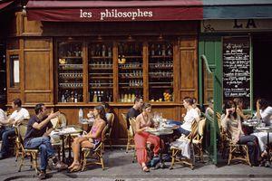 People dine on a cafe terrace in Paris