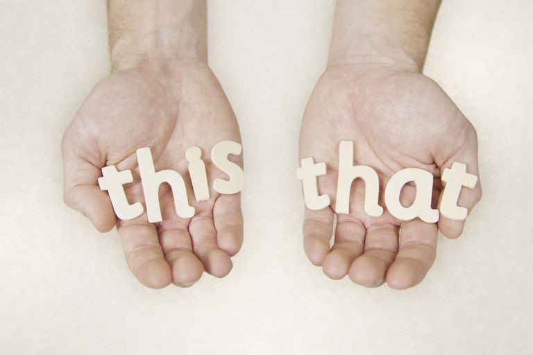 "Hands holding block letters that read ""this"" and ""that"""