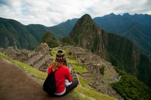 A woman sitting with her back to the camera, looking over Machu Picchu, Peru