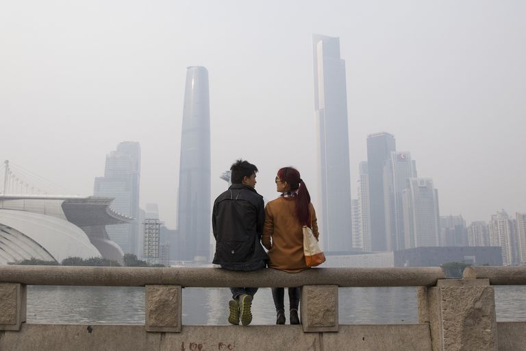 Chinese couple sitting on a bridge in front of a city skyline.