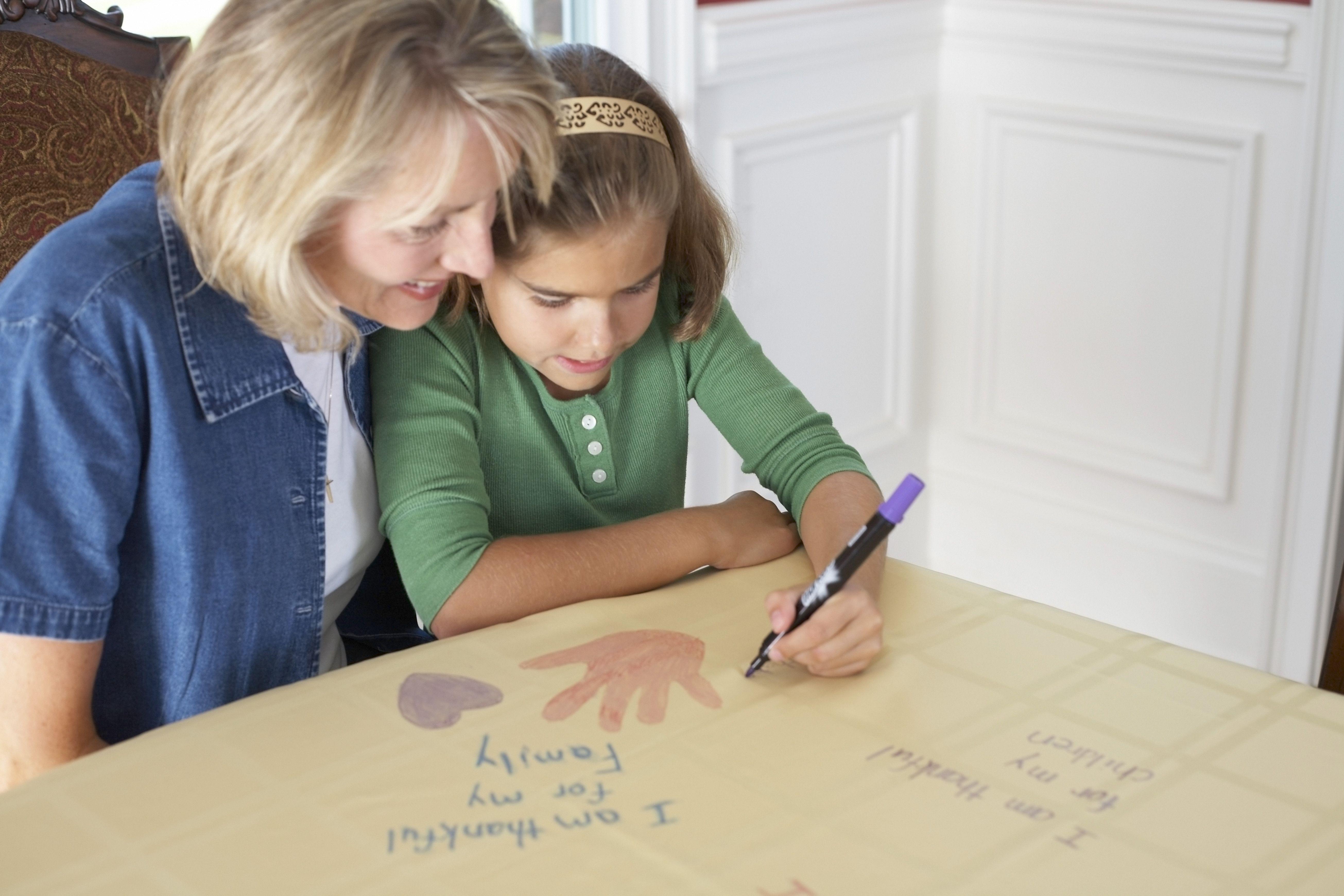 Ein Mädchen mit ihrer Mutter, die ein Bild zeichnet, das sagt, dass ich für meine Familie dankbar bin