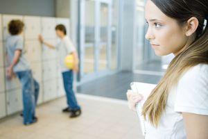 Teenage girl holding notebook, looking away, two teen boys standing near lockers in background