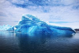 Image of an iceberg floating in the ocean near Greenland