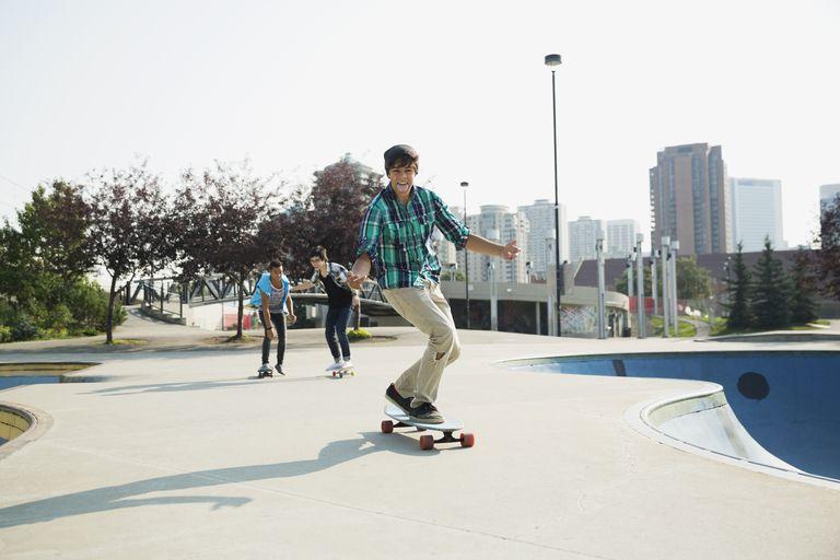 Teenage boys skateboarding at skateboard park