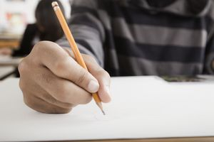 A student's hand writing with pencil