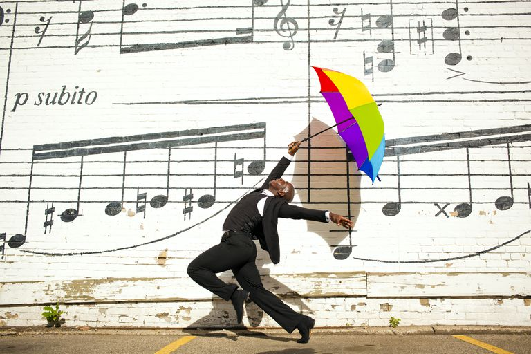 A man jumping and dancing with an umbrella outside